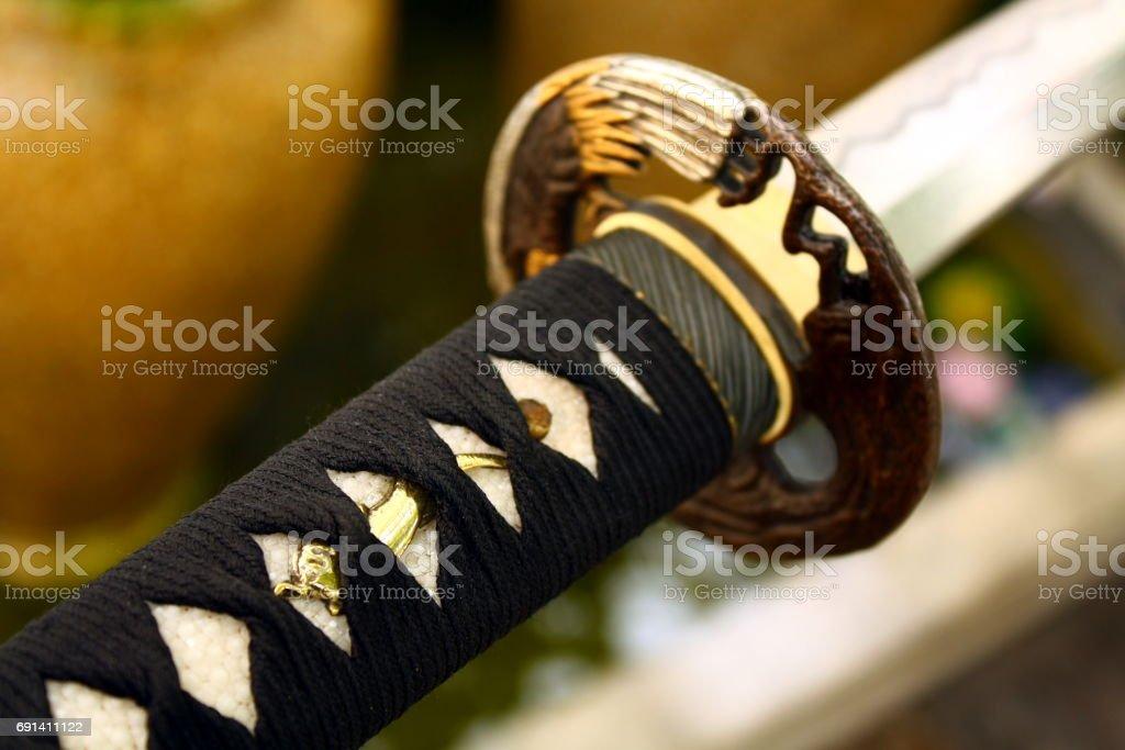Tsuba : hand guard of Japanese sword in garden background stock photo