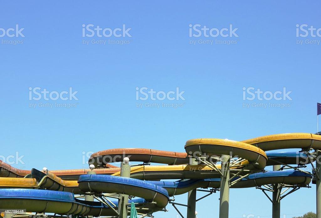 Tube slides at water park against blue sky stock photo