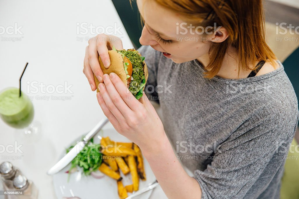 Tucking in to a Healthy Veggie Burger stock photo