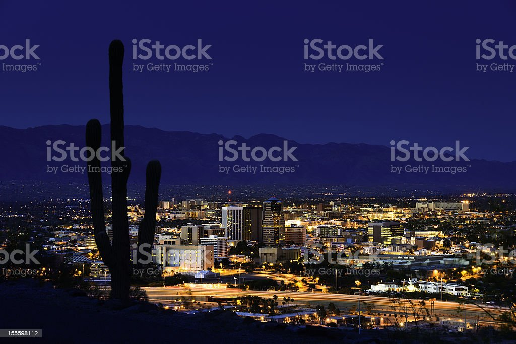 Tucson Arizona at night framed by saguaro cactus and mountains stock photo