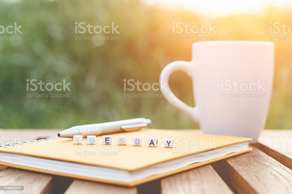 Tuesday written in letter beads and a coffee cup stock photo