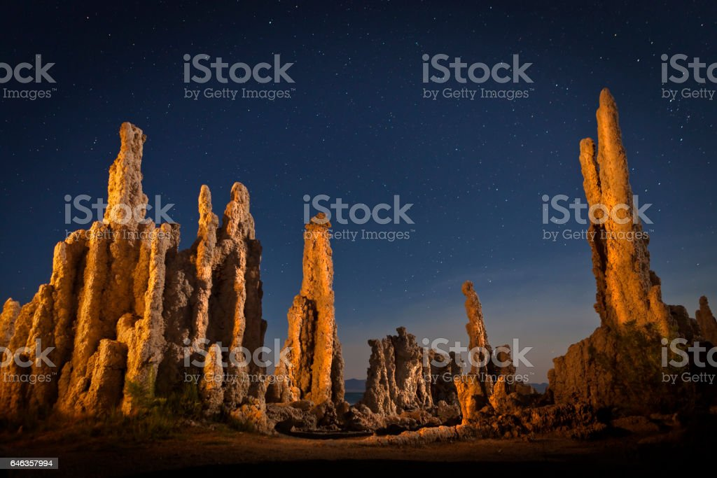 Tufa formation at Mono Lake at night with stars in the sky. Shallow depth of field with focus on lit prominent rock formations stock photo