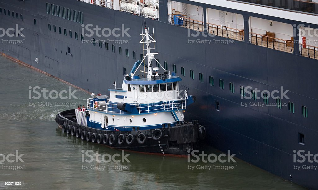 Tug Boat at Work Guiding Large Ship in Harbor royalty-free stock photo