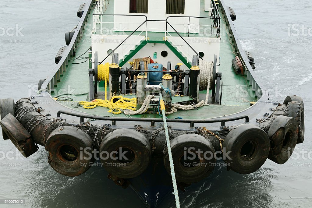Tug boat attached to large ship stock photo
