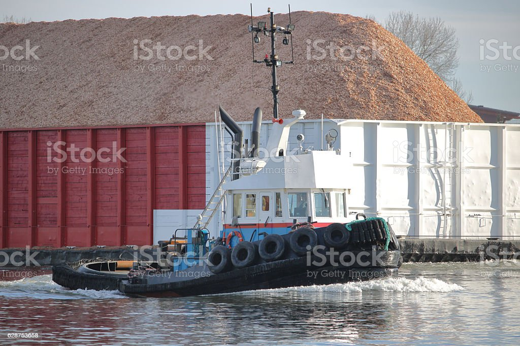 Tug Boat Navigating Barge stock photo