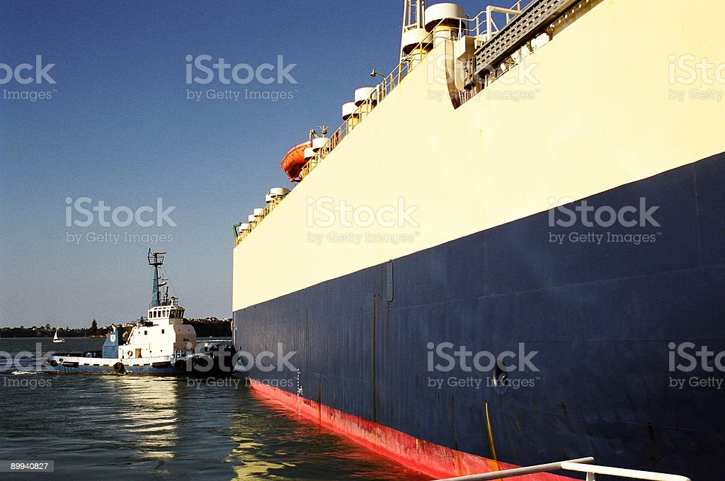 tug boat pushes container ship royalty-free stock photo
