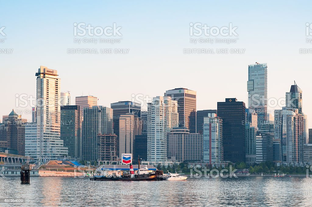 Tug boat refuelling in front of Vancouver skyline at dusk stock photo