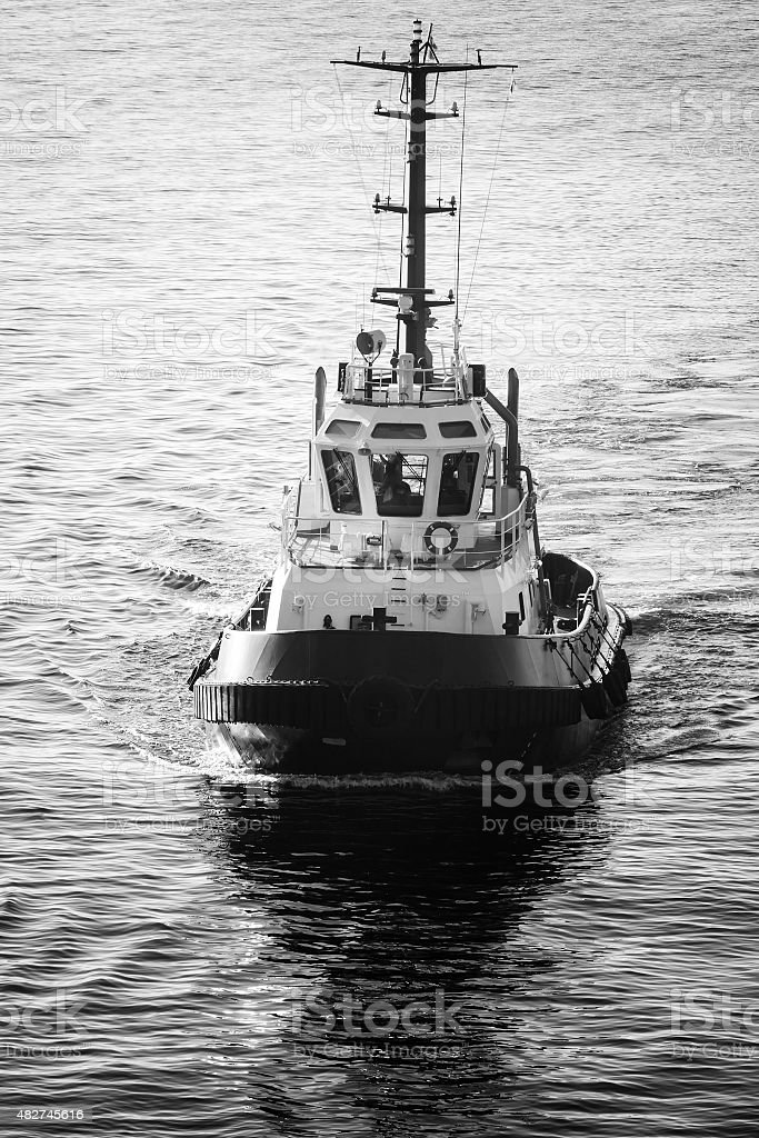 Tug boat underway, front view, black and white stock photo