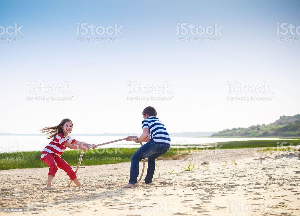 Tug of war - boy and girl playing on beach stock photo