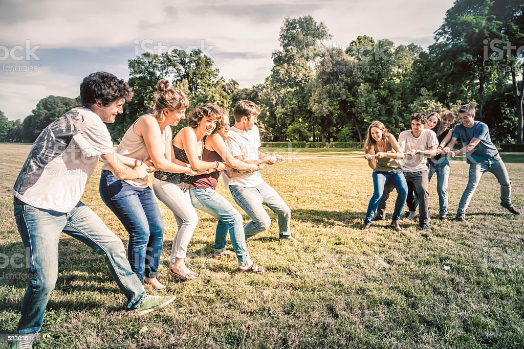 Tug of war - Ten young friends at the park stock photo