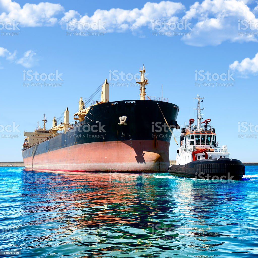 Tugboat and cargo ship stock photo
