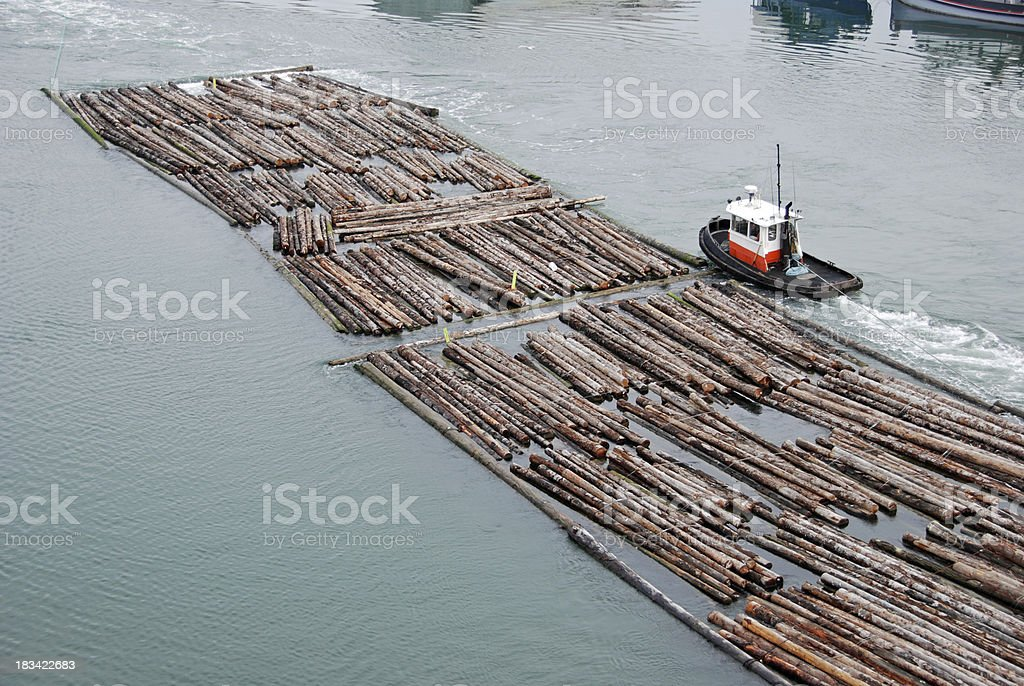 Tugboat and log rafts on river stock photo