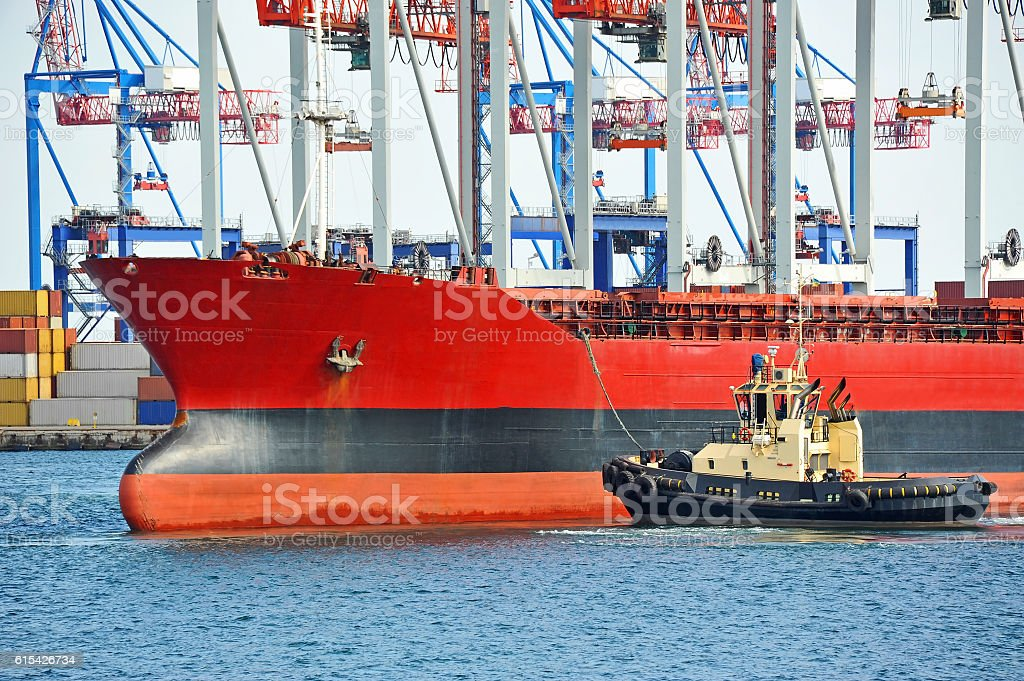 Tugboat assisting bulk cargo ship stock photo