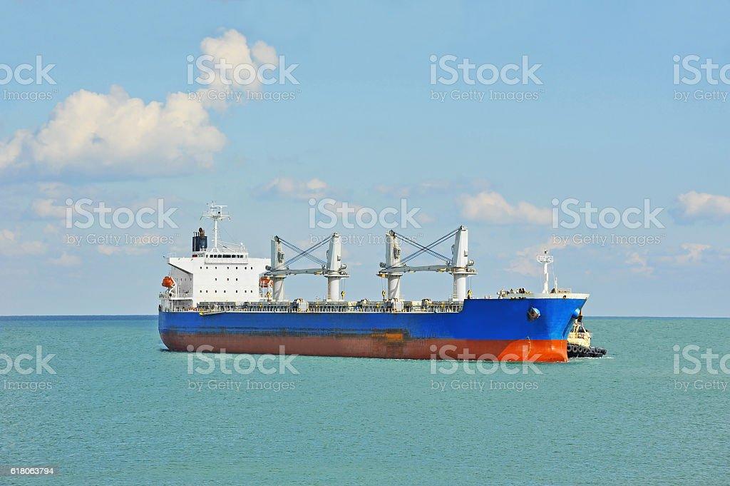 Tugboat assisting bulk cargo ship stock photo