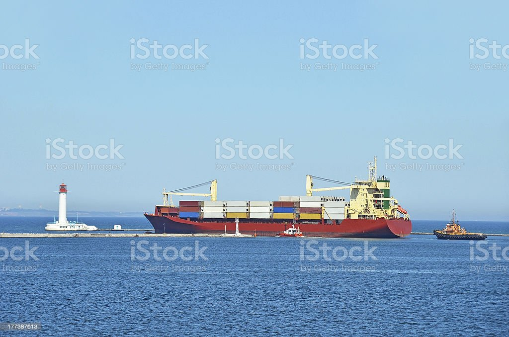 Tugboat assisting cargo ship royalty-free stock photo