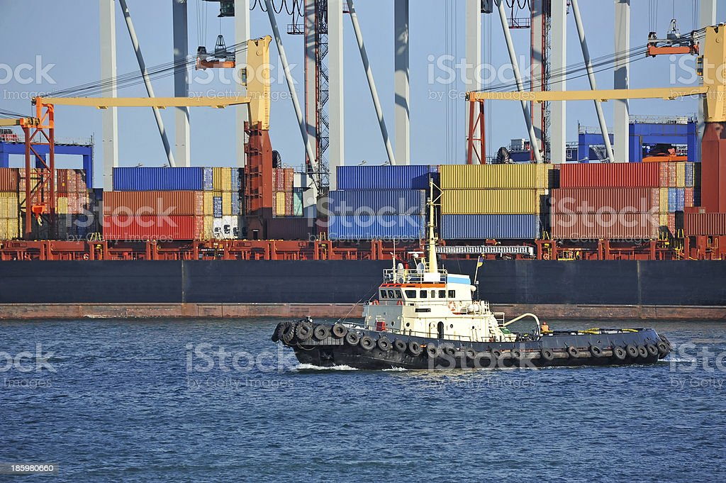 Tugboat assisting container cargo ship royalty-free stock photo