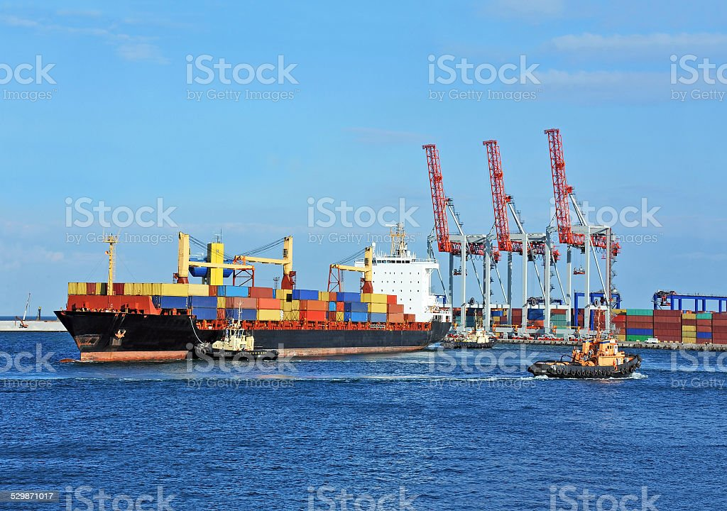 Tugboat assisting container cargo ship stock photo