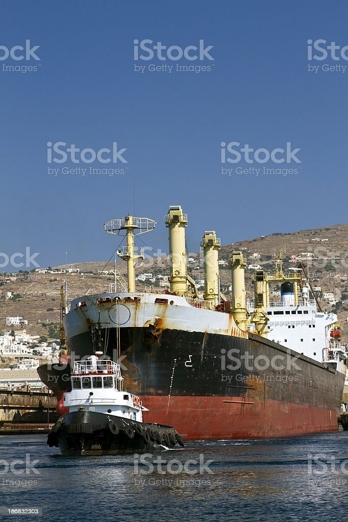 Tugboat at work with a ship in a harbor royalty-free stock photo