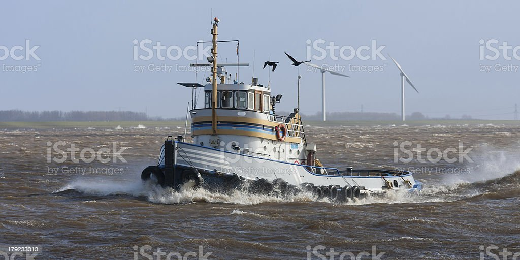 Tugboat crossing the storm stock photo