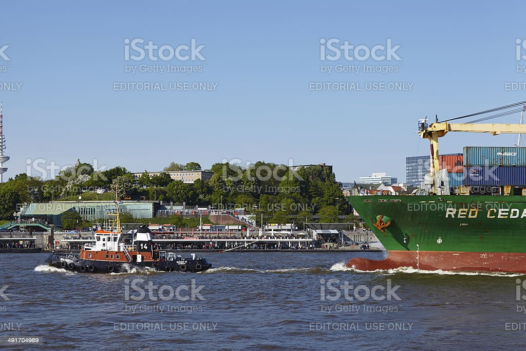 Tugboat drwas a container vessel stock photo