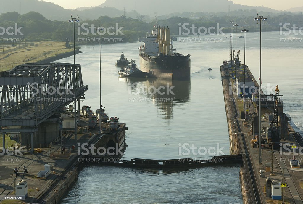 Tugboat Guides Industrial Ship Into Panama Canal Lock royalty-free stock photo