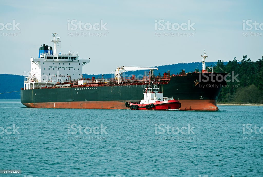 Tugboat guiding ship to oil refinery in Washington state stock photo