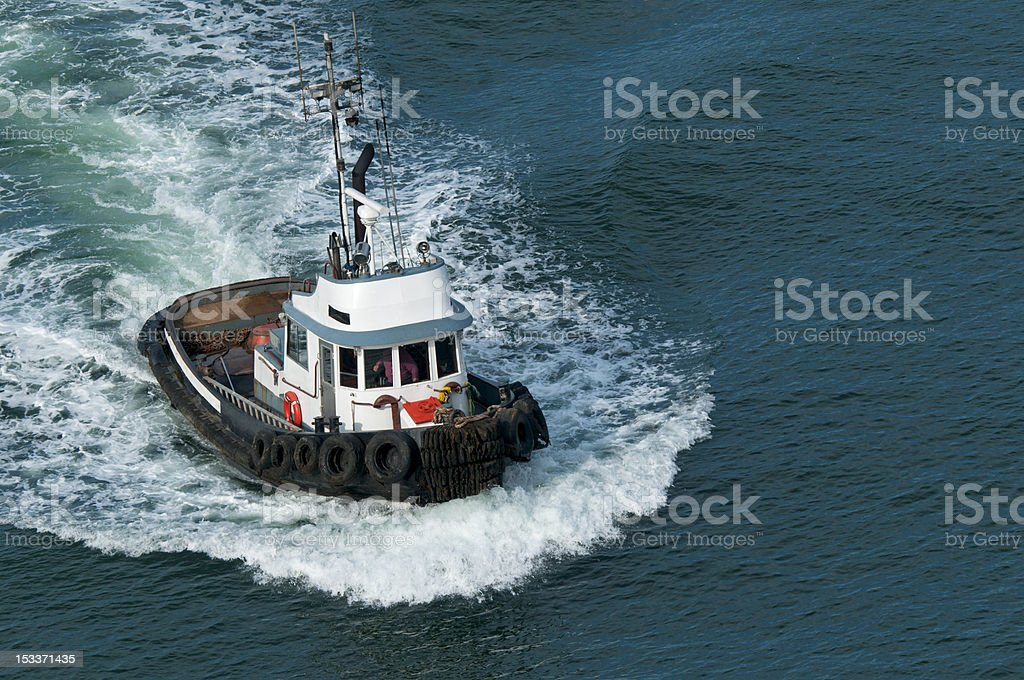 A tugboat on open water traveling fast through the sea stock photo