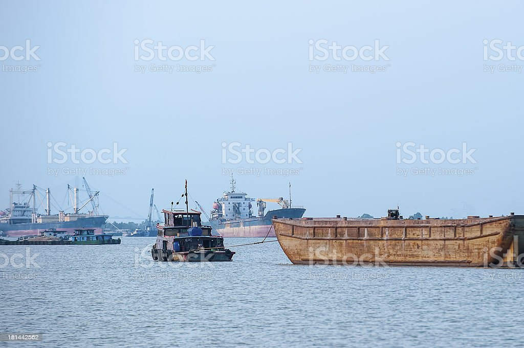 Tugboat pulls container barge down the river stock photo