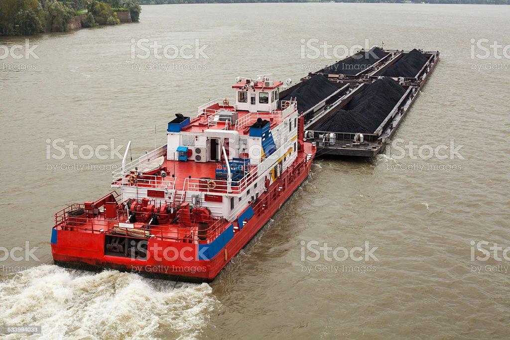 Tugboat Pushing a Heavy Barge stock photo