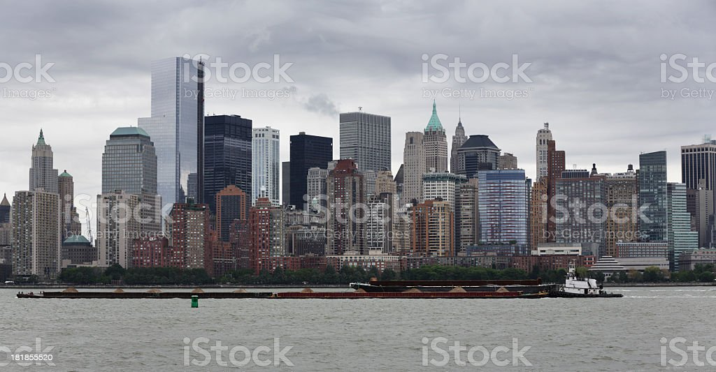 Tugboat Pushing Barges Past Manhattan Skyscrapers royalty-free stock photo