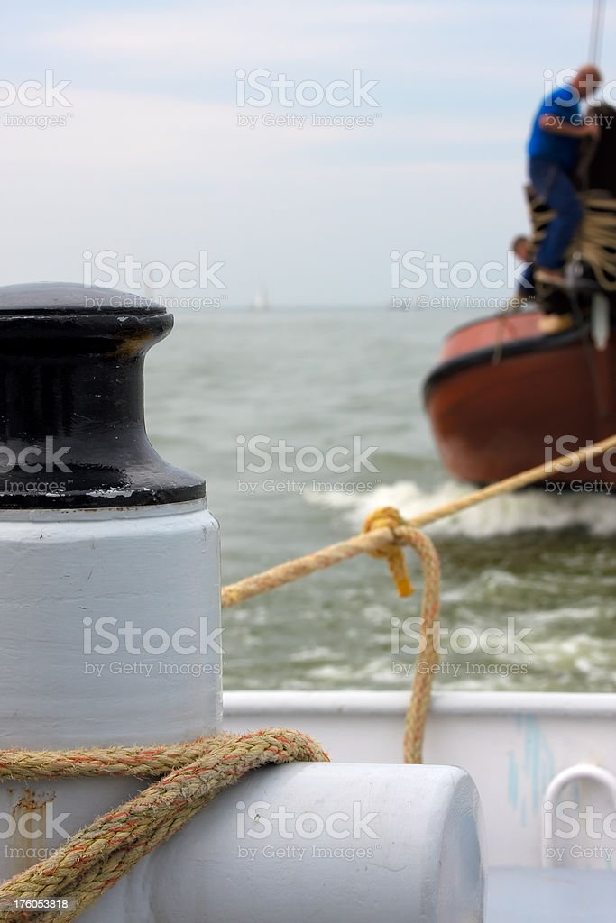 Tugboat towing a traditional sailing vessel. royalty-free stock photo