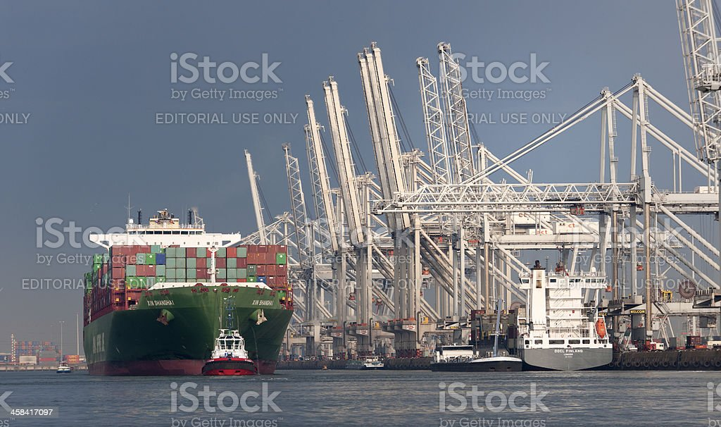 tugboat towing cargo container ship in commercial dock stock photo