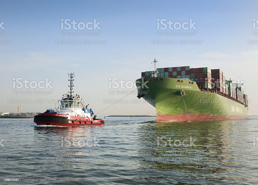 tugboat towing cargo container ship royalty-free stock photo