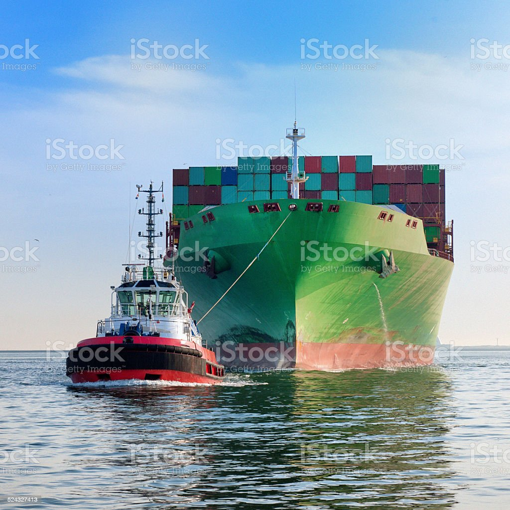 tugboat towing cargo container ship stock photo