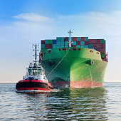 tugboat towing cargo container ship