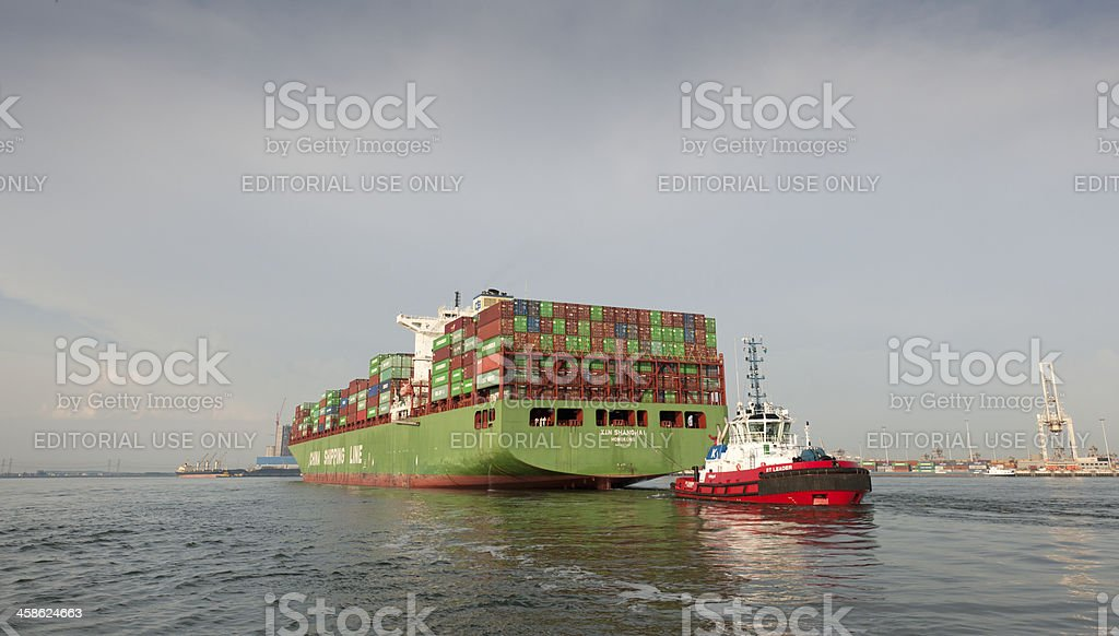 tugboat towing container ship in harbor stock photo
