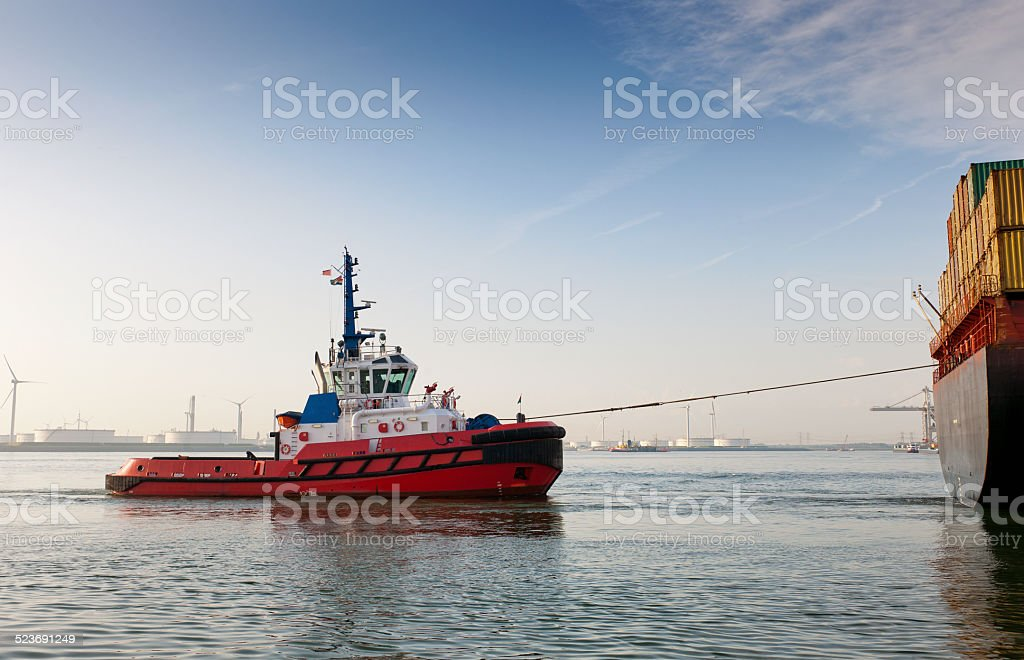 tugboat towing container ship in harbour stock photo