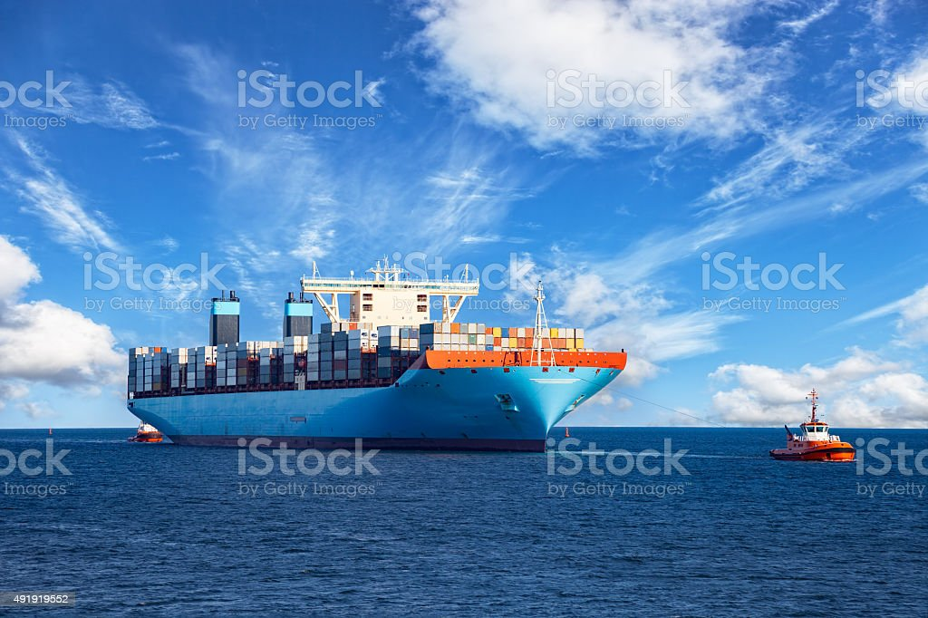 Tugboat towing container ship stock photo