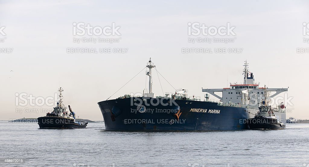 tugboat towing crude oil tanker into harbor stock photo