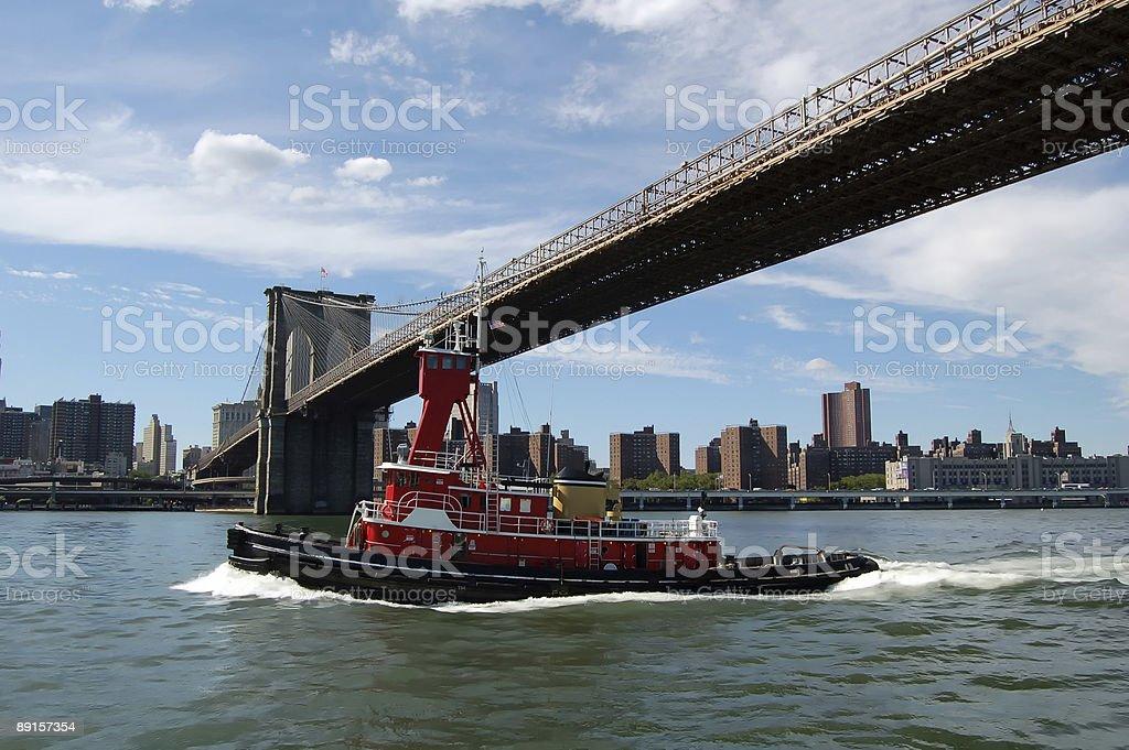 Tugboat under Brooklyn Bridge royalty-free stock photo