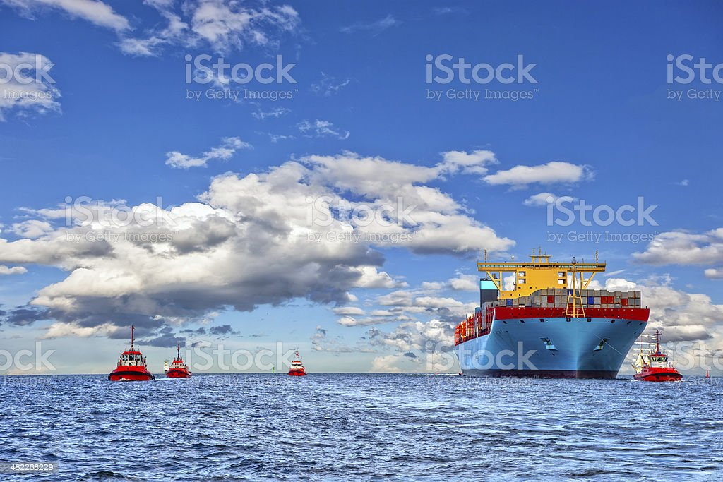 Tugboats and container ship stock photo