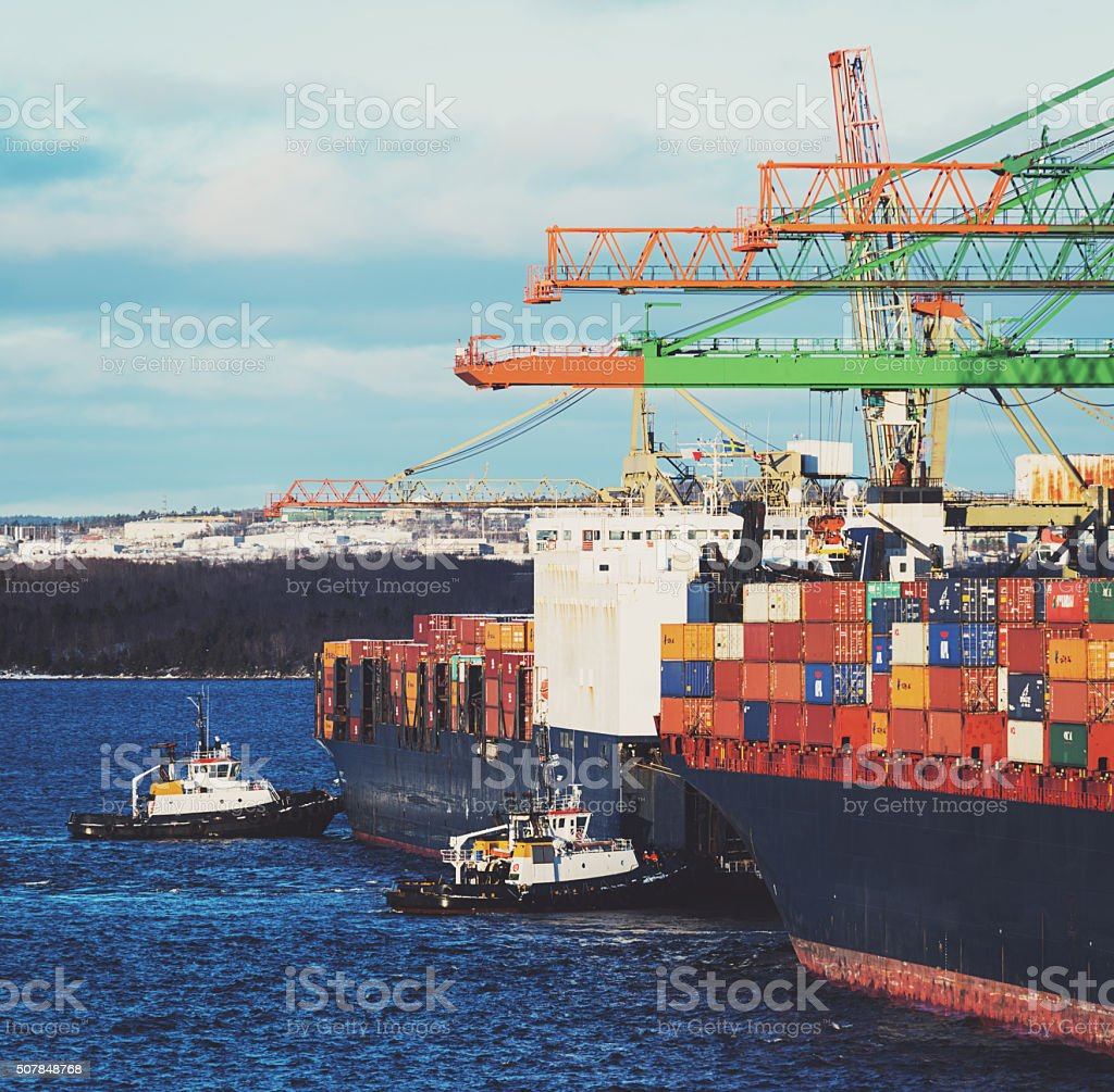 Tugboats Assist Container Ship stock photo