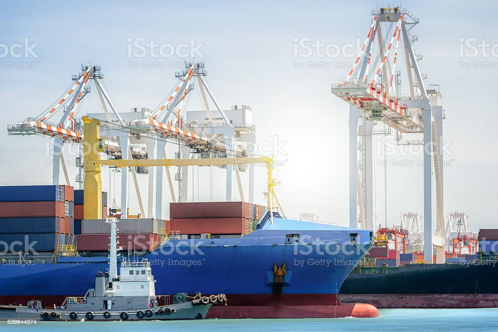Tugboats assisting container cargo ship to harbor. stock photo