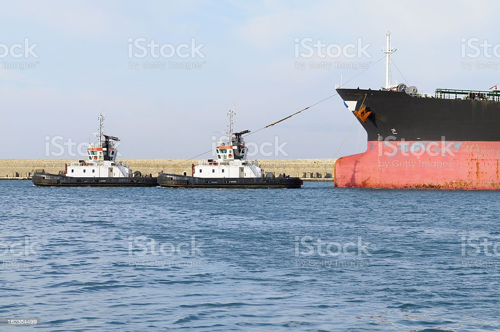 Tugboats towing oil tanker royalty-free stock photo