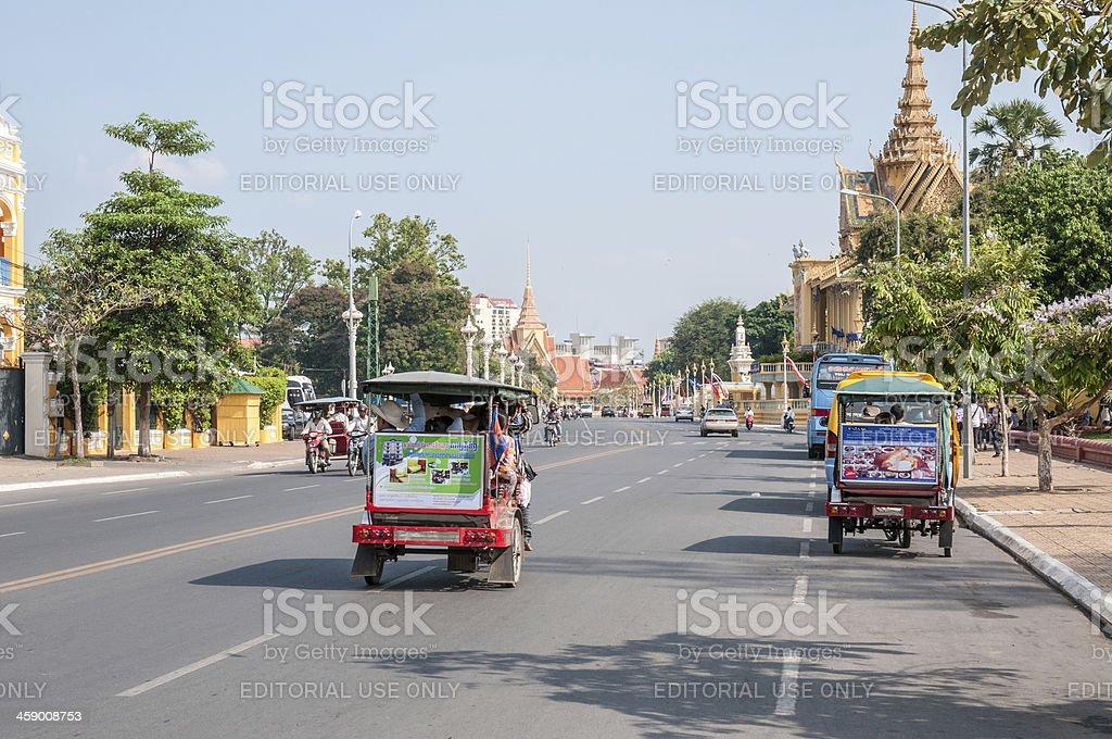 Tuktuks Driving Passed The Royal Palace In Phnom Penh stock photo