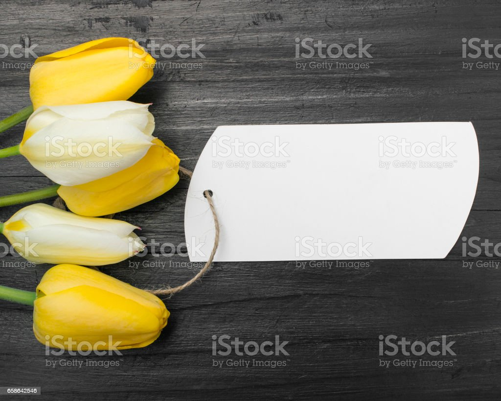 tulip bouquet and blank card on dark wooden table stock photo