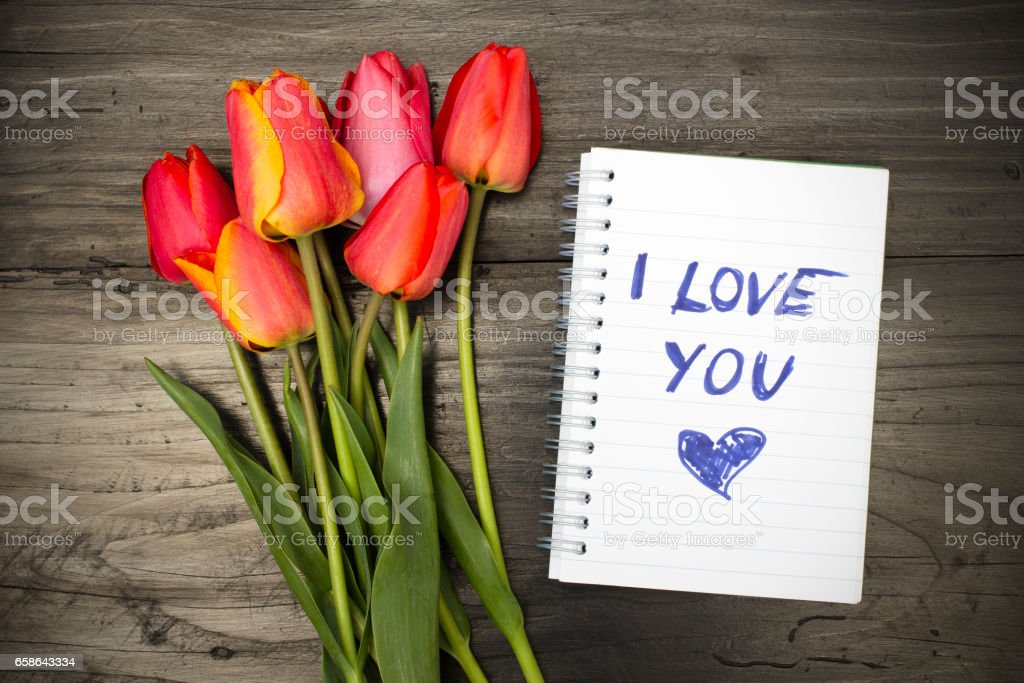 tulip bouquet and notepad with words 'I love you' stock photo