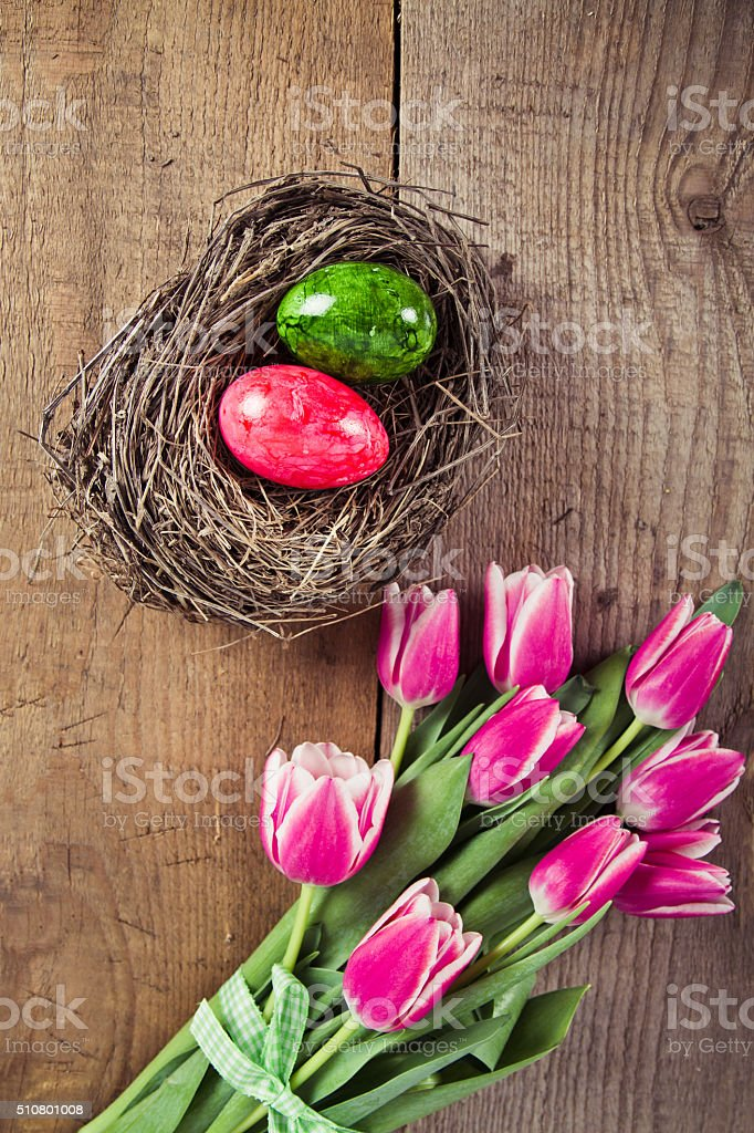 tulips and decorated eggs in the nest stock photo