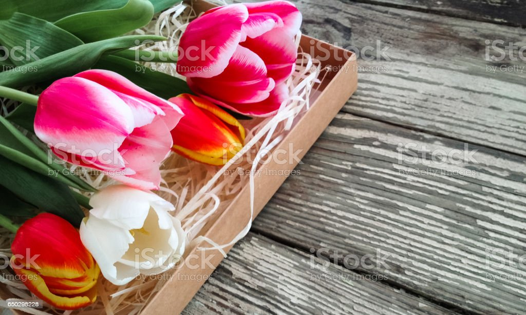 Tulips flowers bunch on an old wooden table stock photo