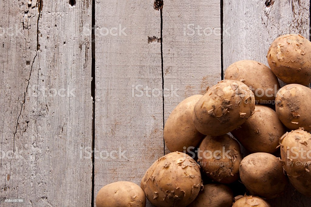 Tumble of Potatoes on Wood stock photo